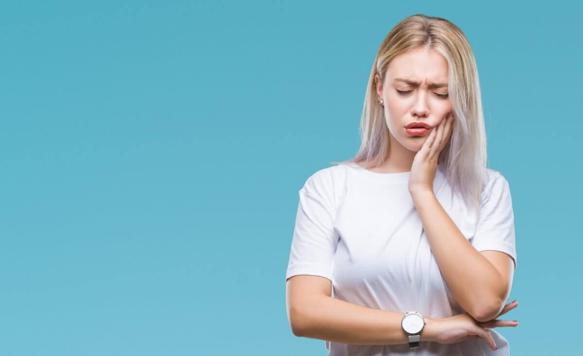 Blonde woman wearing a watch and a short sleeved shirt holding her mouth in pain in front of a blue background.