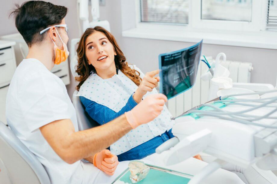 Female patient asking male dentist about x-ray during dental exam